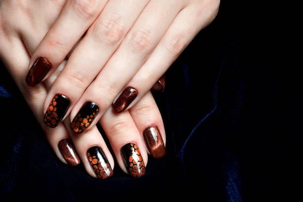 """french maniküre - schöne gepflegte weibliche hände mit braunen """"katzenauge"""" maniküre auf dunklem hintergrund - nailstudio stock-fotos und bilder"""