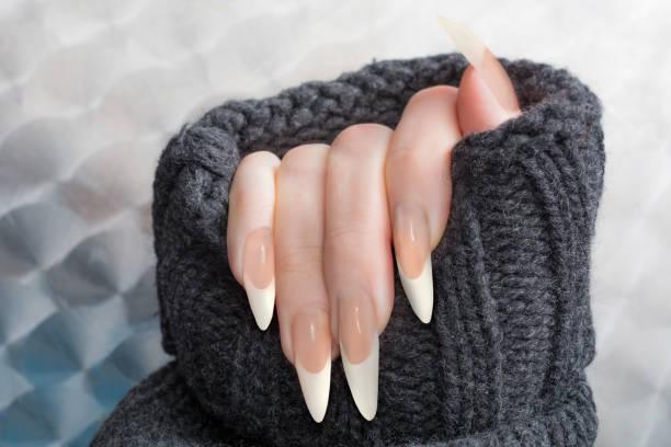 französische maniküre geformt stiletto nägel in warme strickjacke - nails stiletto stock-fotos und bilder