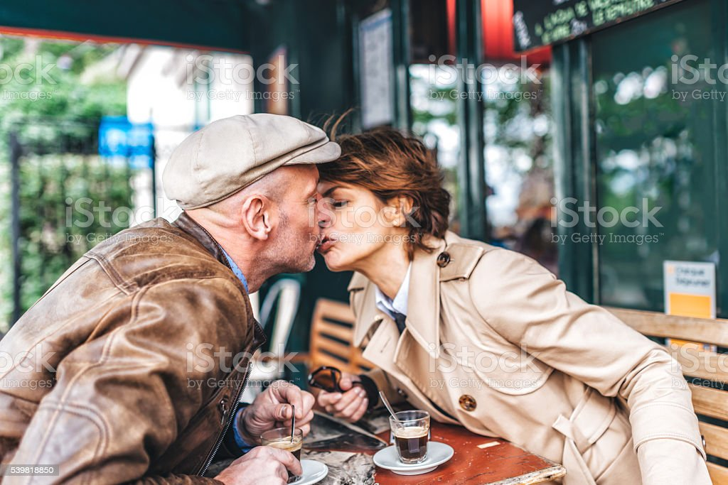 french married couple kissing in paris street cafe stock photo