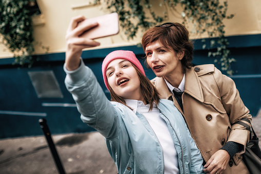 french mother and daughter taking selfie on Paris street