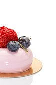 French mousse cake covered with pink glaze on white background. Modern European dessert topped with blueberries and strawberry. Isolated on white.