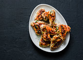 French mustard marinade roasted chicken wings - delicious appetizers, tapas on dark background, top view