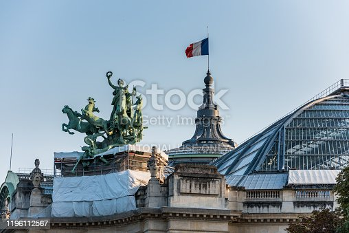 Paris, France - August 23, 2018: French National Flag  and statue on The Grand Palais in Paris, currently the largest existing ironwork and glass structure in the world