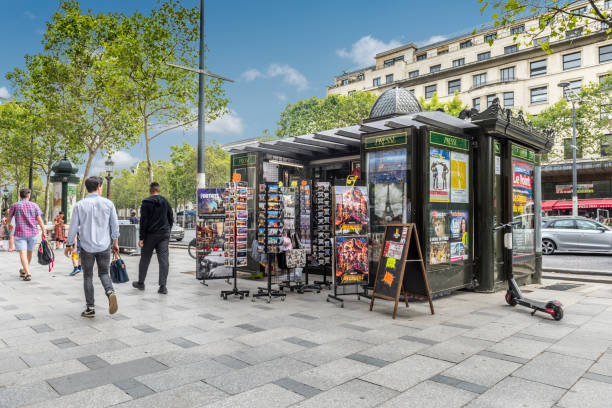 French newstand Paris, France - August 2, 2019: Tourists and passersby around a press kiosk and souvenirs in the Champs Élysées of Paris France. news stand stock pictures, royalty-free photos & images