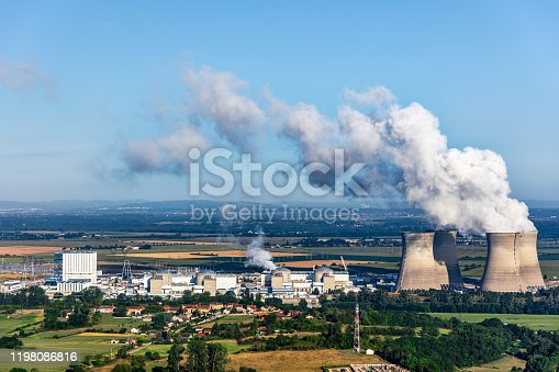 Photography of french nuclear power station with four steaming cooling towers smoking on blue sky in summer, in Ain department countryside plain with water condensation. Image taken from high angle view, aerial view, in Bugey, in Ain on the border of Isere department, Auvergne-Rhone-Alpes region in France (Europe). The nuclear power station is located in the middle of a plain landscape in France, near Lyon city. Shot in sunny day summer season with green meadows near small villages.