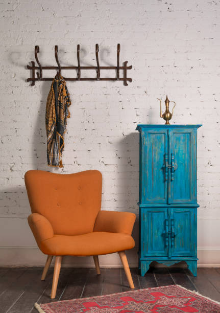 French orange wingback armchair, vintage cupboard, and wall hanger with ornate scarf on bricks wall stock photo