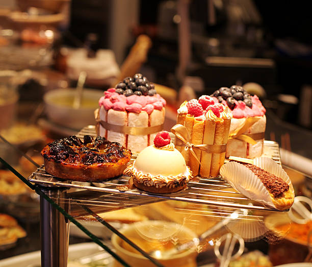 french pastries on display a confectionery shop - bakery stockfoto's en -beelden