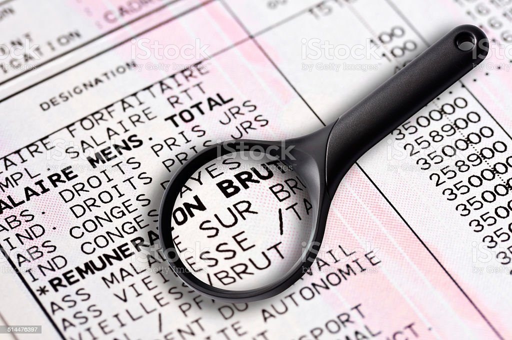 French payslip and magnifying glass close-up stock photo