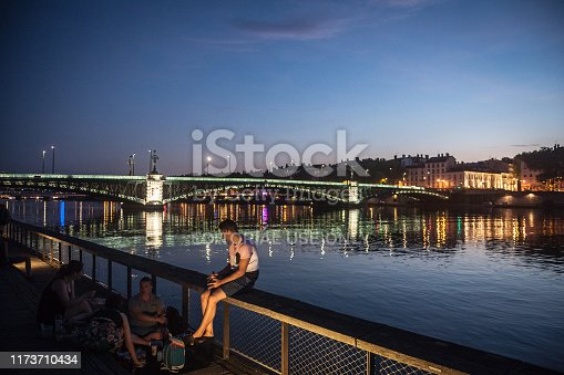 Picture of people sitting on the quays of the riverbank of the Rhone river in the evening to drink alcohol. Lyon is the second biggest city of France.