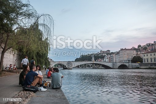 Picture of people sitting on the quays of the riverbank of the Saone river in the evening to drink alcohol. Lyon is the second biggest city of France.