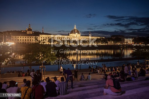 Picture of the Hotel Dieu at Dusk, with people sitting on the quays of the riverbank of the Rhone river in the evening to drink alcohol. Hotel-Dieu de Lyon was a hospital of historical significance situated on the west bank of the Rhone river transformed into a luxury hotel