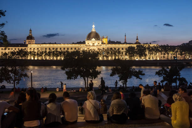 "French people sitting on the riverbank of the Quais De Rhone, facing Hotel Dieu, one of the main monuments of the city for the tradition of apero Picture of the Hotel Dieu at Dusk, with people sitting on the quays of the riverbank of the Rhone river in the evening to drink alcohol. Hotel-Dieu de Lyon was a hospital of historical significance situated on the west bank of the Rhone river transformed into a luxury hotel""n""n main de dieu stock pictures, royalty-free photos & images"