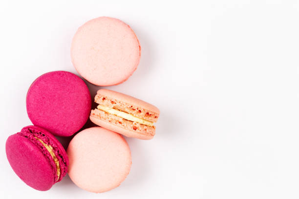 French pink and magenta macarons or macaroons, top view on a white background with copyspace stock photo