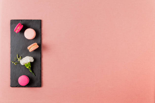 French pink macarons or macaroons, and incarnation white flower on a slate over a pink tablecloth background with copyspace. stock photo