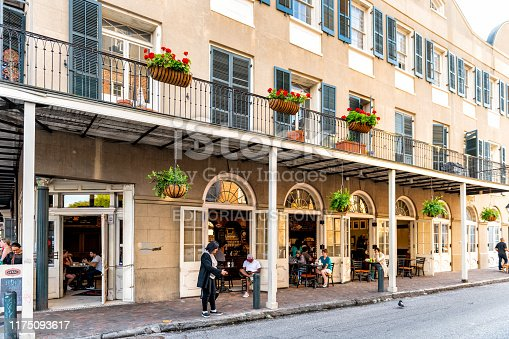 938895626 istock photo French Quarter street covered sidewalk with people eating and sitting at sidewalk outdoor Envie cafe or restaurants at Louisiana old town city 1175093617