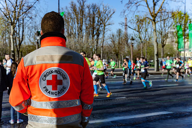 French red cross man supervising runnrers stock photo