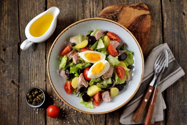 French salad Nicoise with tuna, boiled potatoes, egg, green beans, tomatoes, dried olives, lettuce and anchovies. Top View. stock photo