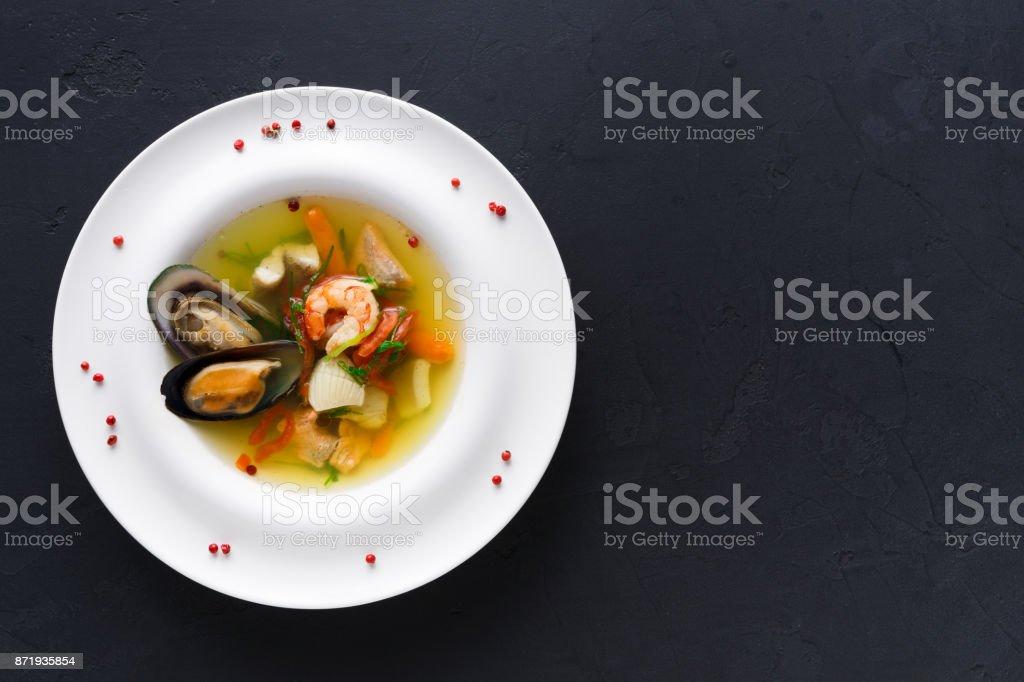 Französische Meeresfrüchtesuppe mit weißem Fisch, Garnelen und Muscheln in Platte am hölzernen Hintergrund – Foto