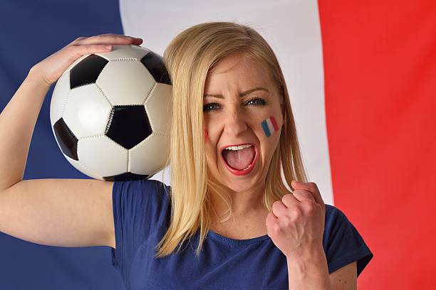 French soccer fan cheers football team in the national colors. stock photo