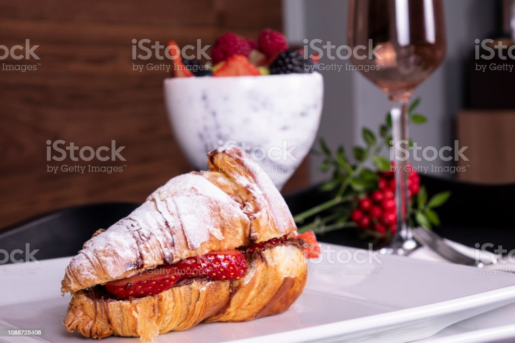 French style romantic summer picnic setting. Flat-lay of glasses of rose wine, fresh strawberries, croissants, brie cheese, hat, sunglasses, peony flowers, square crop. stock photo
