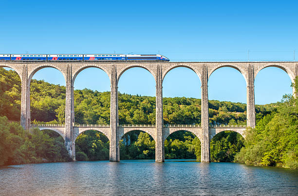 French TGV train on stone viaduct in Rhone-Alpes France Cize, France - July 9, 2015: French high speed train TGV operated by SNCF, national rail operator on Cize-Bolozon viaduct bridge in Ain, Rhone-Alpes region in France. This train was developed during the 1970s by GEC-Alsthom and SNCF. A TGV test train set the record for the fastest wheeled train, reaching 574.8 km/h (357.2 mph) on 3 April 2007. Viaduct of Cize-Bolozon in summer season in Bugey along Ain river. This viaduct is a combination rail and vehicular viaduct crossing the Ain gorge. An original span built in the same location in 1875 was destroyed in World War II. Reconstructed as an urgent post-war project due to its position on a main line to Paris, the new viaduct reopened in May 1950. It carries road and rail traffic at different levels. railway bridge stock pictures, royalty-free photos & images