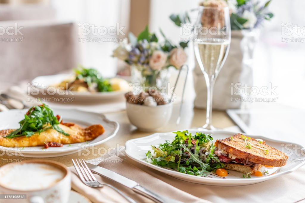 French toast brioche, Sandwich with pastrami and sun-dried tomatoes. Light morning Breakfast, fresh warm pastries on table in restaurant French toast brioche, Sandwich with pastrami and sun-dried tomatoes. Light morning Breakfast, fresh warm pastries on table in restaurant. Arugula Stock Photo