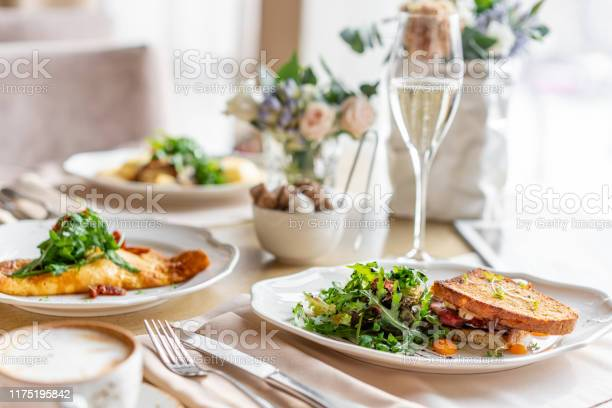 French Toast Brioche Sandwich With Pastrami And Sundried Tomatoes Light Morning Breakfast Fresh Warm Pastries On Table In Restaurant Stock Photo - Download Image Now