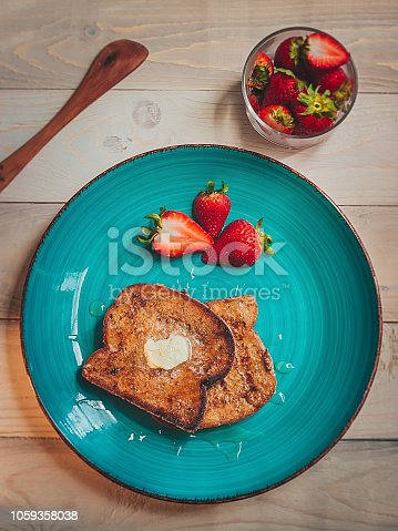 Delicious french toast , strawberries and honey on a wooden table