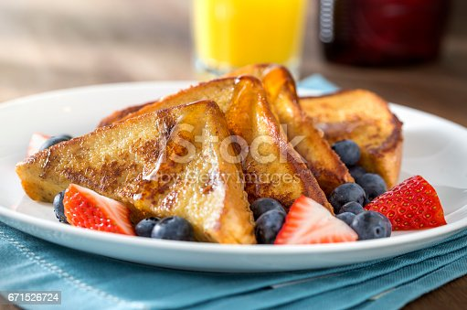 Plate of french toast in the morning light with maple syrup, blueberries, strawberries, and a glass of orange juice on rustic wood table with blue napkin.