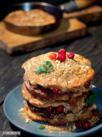 Homemade griddle cakes - hybrid of French toast and buttermilk pancakes with croutons and fresh pears in batter. Served with cranberries and syrup
