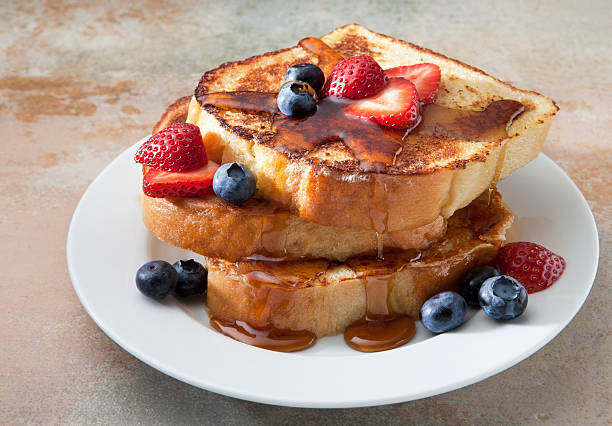French toast with berries and syrup on a marble countertop