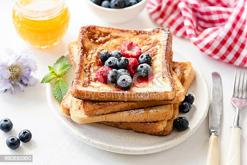Delicious French toast with berries and honey on white plate. Tasty breakfast concept
