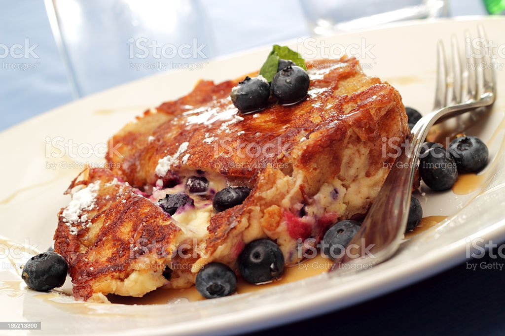 French toast with blueberries on a white plate with a fork stock photo
