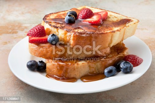 French toast with strawberries and blueberries on a marble countertop.
