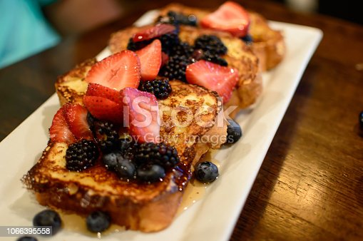 Plate of french toast ready to eat with fresh berry garnish, sliced Strawberry, blueberry and blackberry healthy eating decadent brunch on plate ready to eat