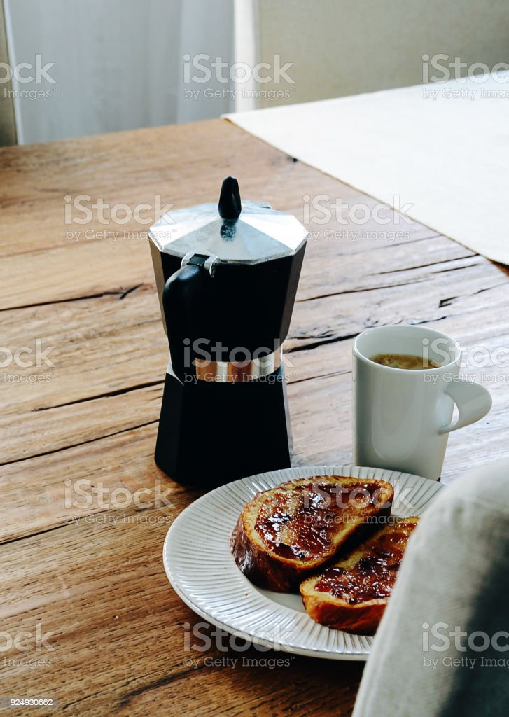 French toasts covered with jam laying on white plate. Coffee mug and...