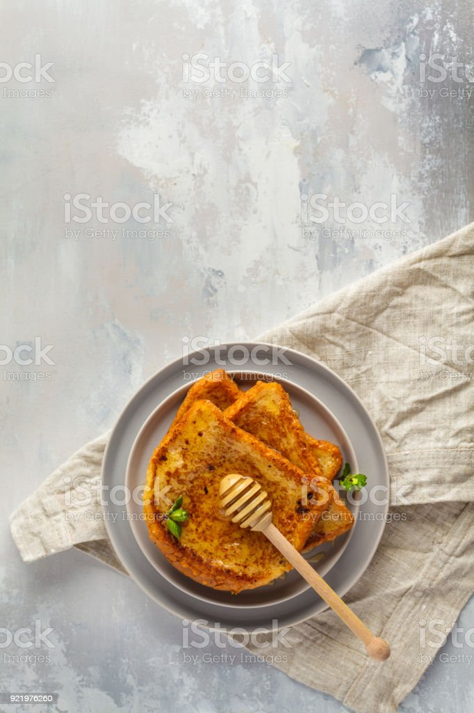 French toasts with honey. Gray background, copy space, top view. stock photo