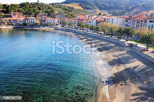 Collioure -  a small town at the Cote Vermeille (mediterranean sea), Department Pyrenees-Orientales in Languedoc-Roussillon, Southern France. The promenade with palm trees at the beach. Sunny winter day.