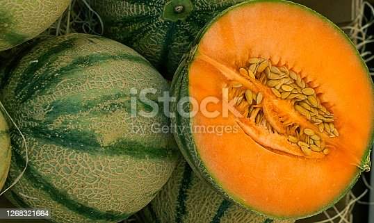 image of an open cantaloupe sliced by halb on top of others uncut cantaloupes