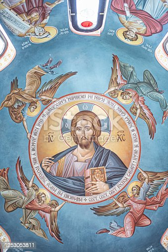 Fresco with religious saint and angels on the ceiling in a church.