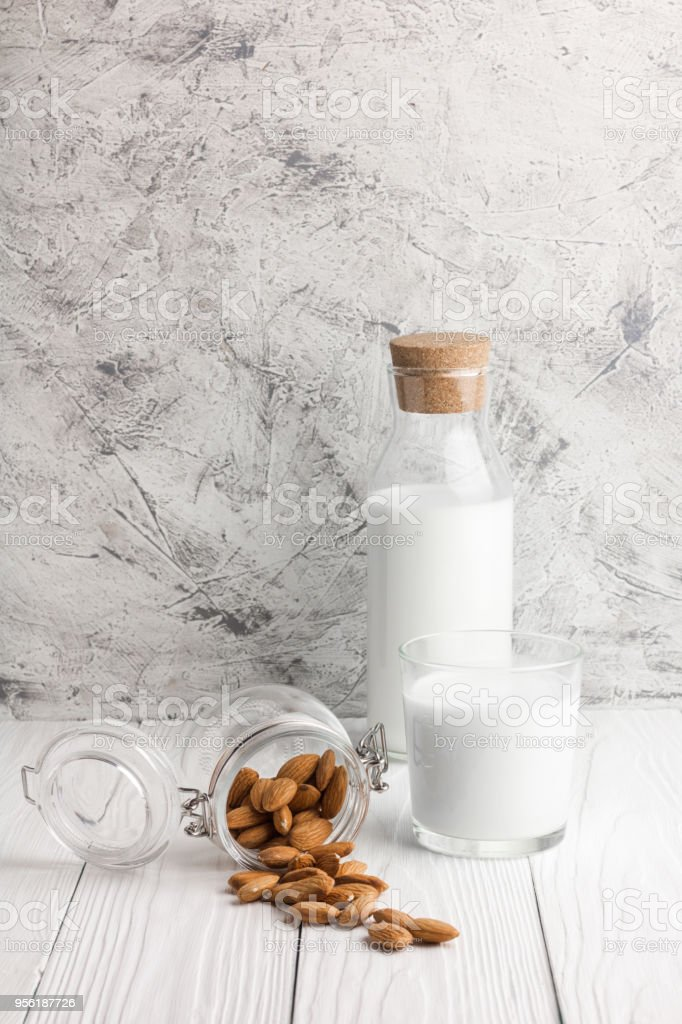 Bottle of almond milk with glass and almonds on rustic white wooden...