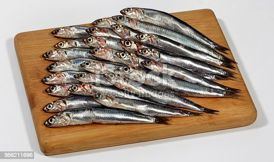 istock Fresh Anchovies fish on wooden cutting board 956211696