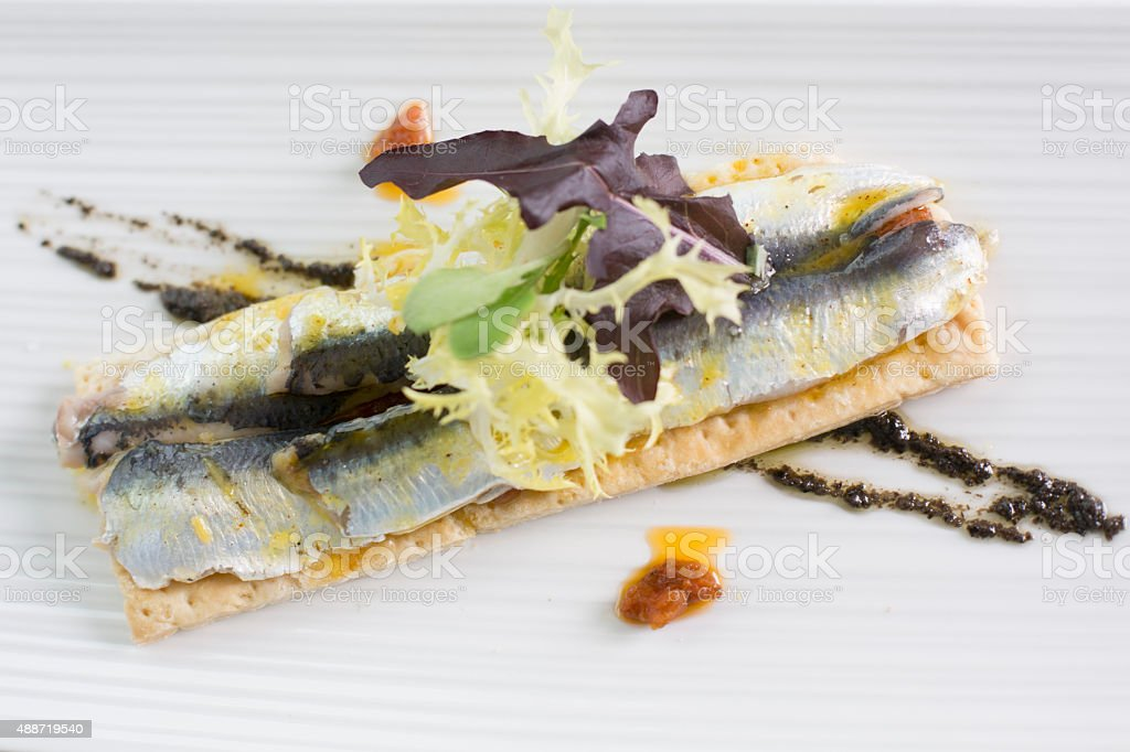 Fresh anchovies on thin bread with black olive vinagrete stock photo