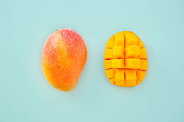 Fresh and beautiful mango fruit with sliced diced mango chunks on a light blue background, copy space(text space), blank for text, top view. Fresh and beautiful mango fruit with sliced diced mango chunks on a light blue background, copy space(text space), blank for text, top view. mango stock pictures, royalty-free photos & images