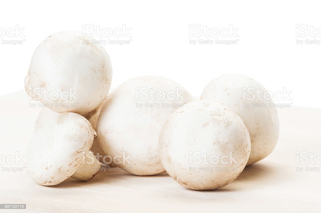 Fresh and clean champignon mushrooms on wooden board stock photo