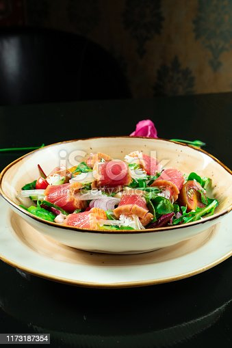 istock Fresh and delicious Tataki salad with tuna, lettuce, red onion, cherry tomatoes and daikon radish. Tasty seafood salad of Japanese cuisine in yellow bowl on dark background. Close up food photo 1173187354