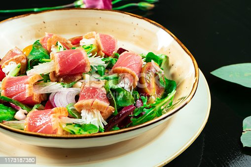 istock Fresh and delicious Tataki salad with tuna, lettuce, red onion, cherry tomatoes and daikon radish. Tasty seafood salad of Japanese cuisine in yellow bowl on dark background. Close up food photo 1173187380