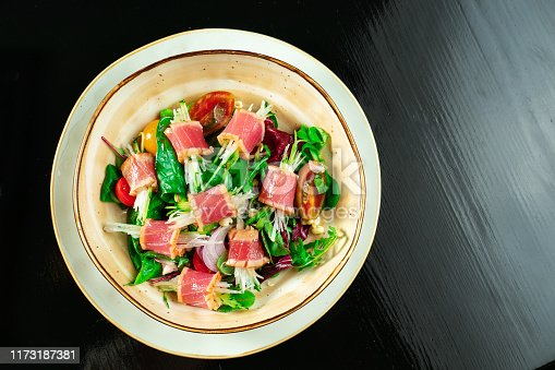 istock Fresh and delicious Tataki salad with tuna, lettuce, red onion, cherry tomatoes and daikon radish. Tasty seafood salad of Japanese cuisine in yellow bowl on dark background. Close up food photo 1173187381