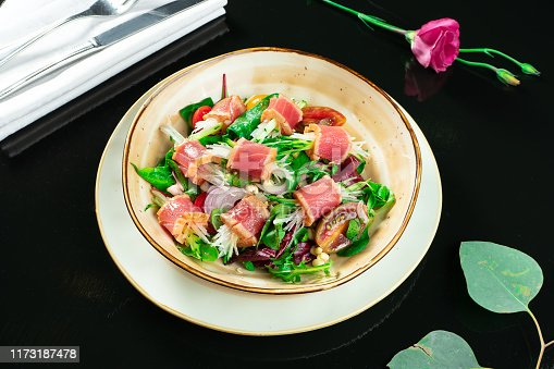istock Fresh and delicious Tataki salad with tuna, lettuce, red onion, cherry tomatoes and daikon radish. Tasty seafood salad of Japanese cuisine in yellow bowl on dark background. Close up food photo 1173187478