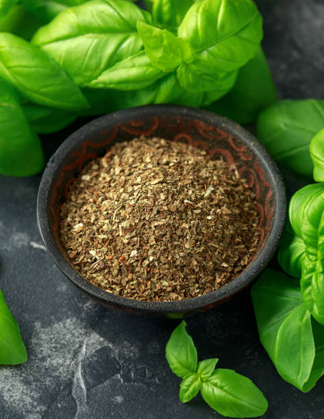 Fresh and dried basil in bowl. on black rustic table stock photo